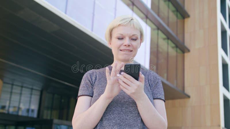 Junge blonde Dame Using ein Telefon in der Stadt stockfotos