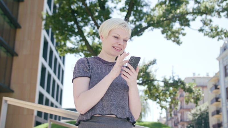 Junge blonde Dame Using ein Telefon in der Stadt lizenzfreies stockfoto