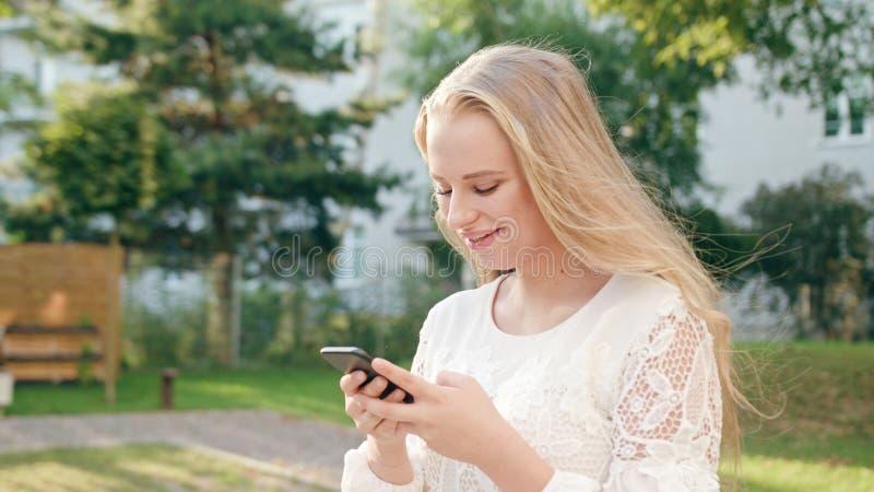 Junge blonde Dame Walking und unter Verwendung eines Telefons in der Stadt stockbild