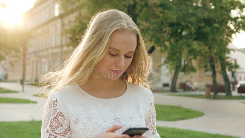 Junge blonde Dame Walking und unter Verwendung eines Telefons in der Stadt lizenzfreie stockbilder