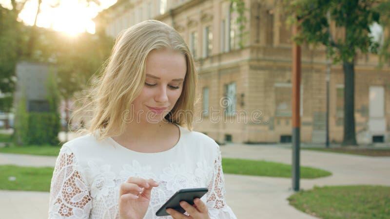Junge blonde Dame Walking und unter Verwendung eines Telefons in der Stadt lizenzfreies stockfoto