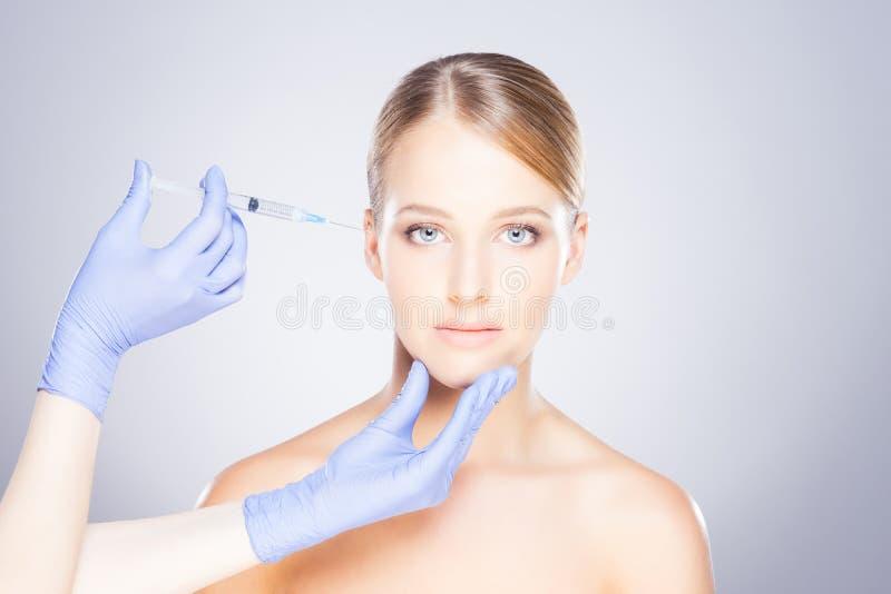 Junge blonde Frau auf einem Gesichtseinspritzungsverfahren stockbild