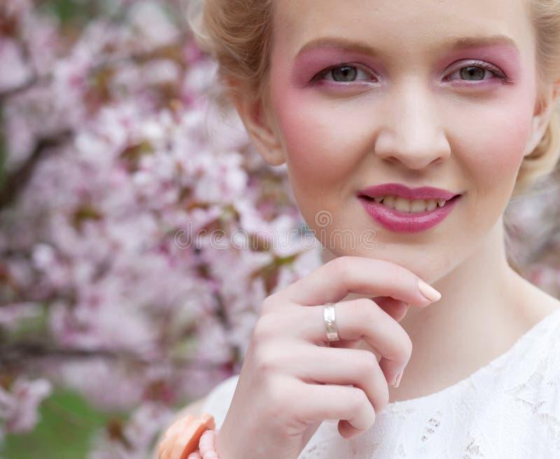 Junge blonde Frau in blühendem Kirschblüte-Garten stockfoto
