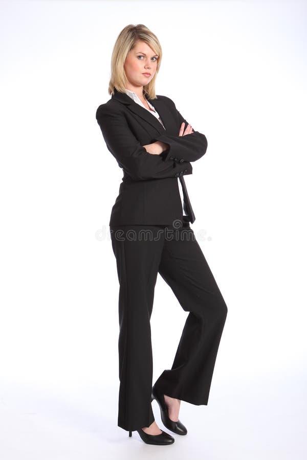 Junge blonde Frau in den Anzugarmen gefaltet stockfotografie