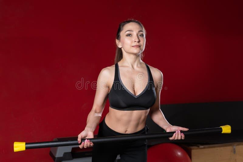 Junge blonde Frau der Eignung hält gymnastischen Körperstangenstock in ihrer Hand in der Turnhalle stockfotos