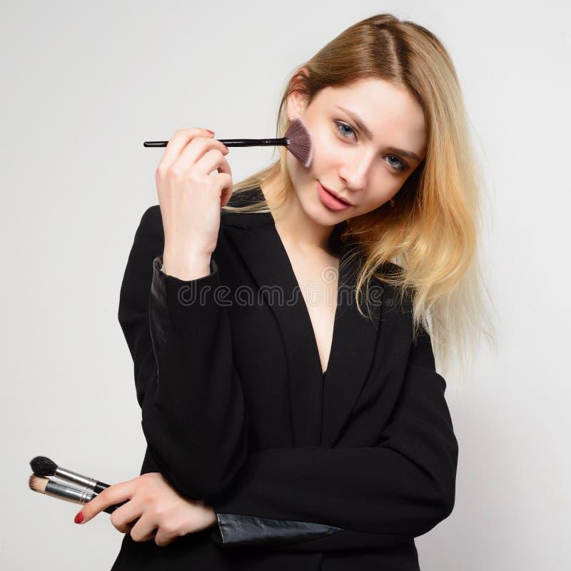 Junge blonde Frau in der schwarzen Jacke macht sich ein Make-up lizenzfreies stockfoto