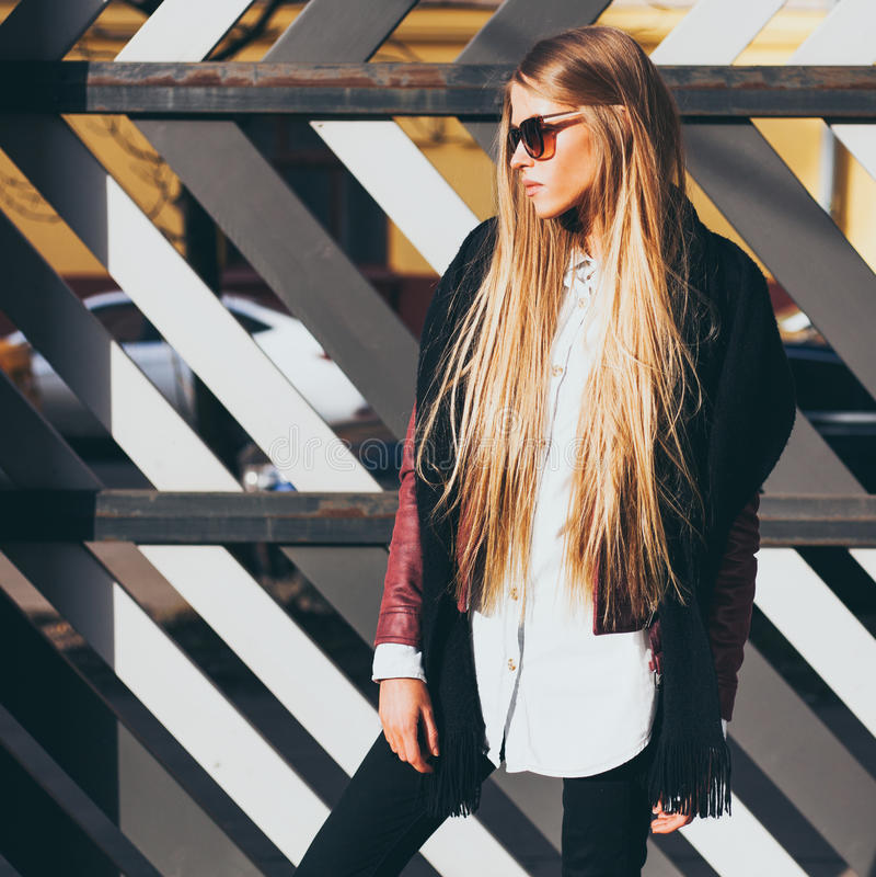 Junge blonde Frau in der Sonnenbrille und eine moderne Ausstattung, die am warmen Frühlingsabend der Straße aufwirft Mode Blogger lizenzfreie stockfotografie