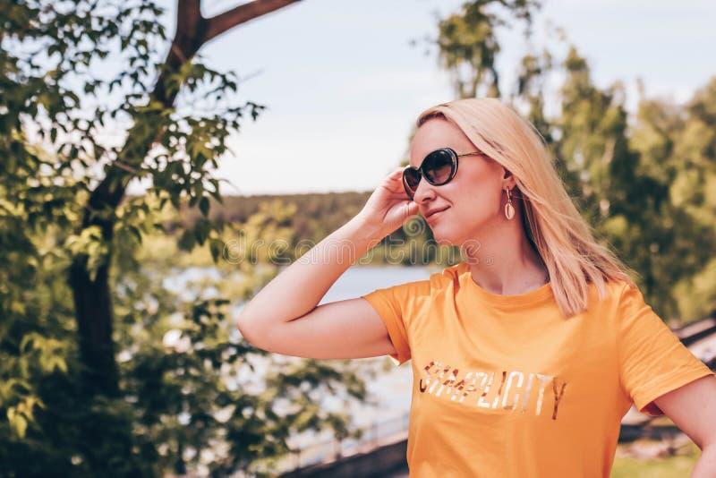 Junge blonde Frau in der Sonnenbrille und in yallow T-Shirt, das draußen an einem sonnigen Tag aufwirft stockfotos
