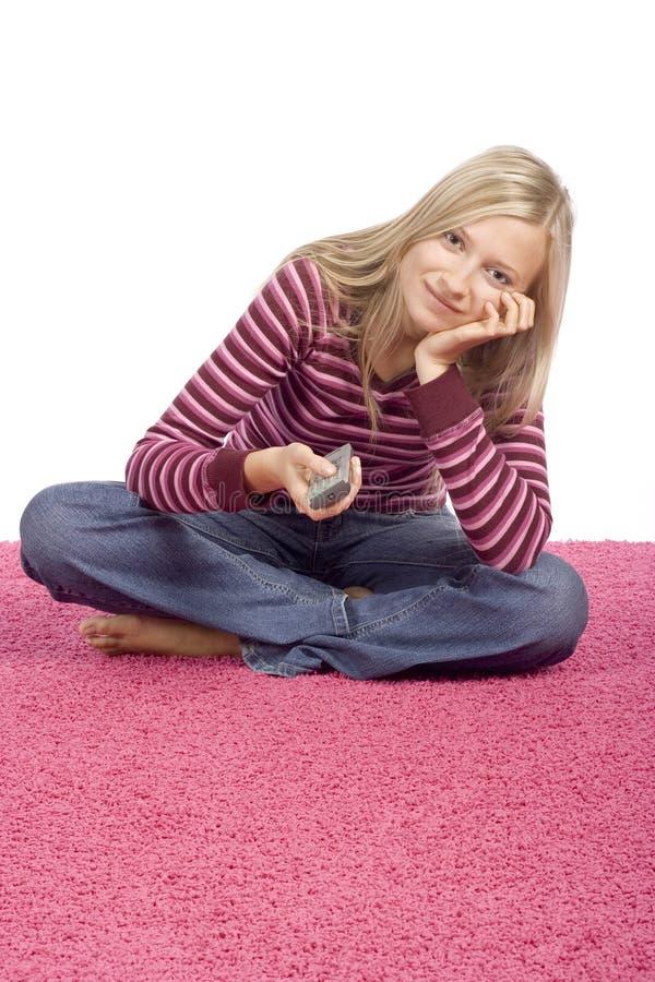 Junge blonde Frau, die auf dem rosafarbenen Teppich mit Ferncontro sitzt lizenzfreie stockfotos