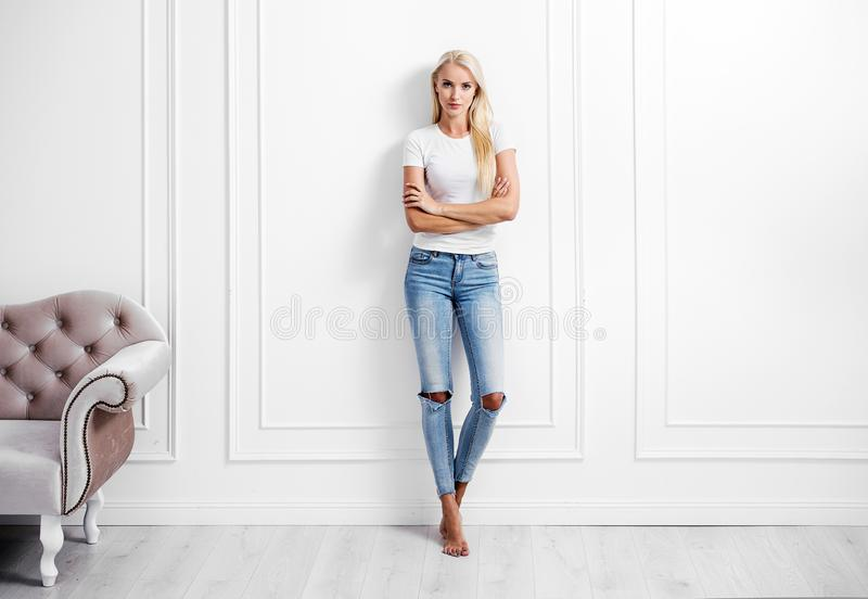 Junge blonde Frau, die auf einer dekorativen Wand sich lehnt lizenzfreies stockbild