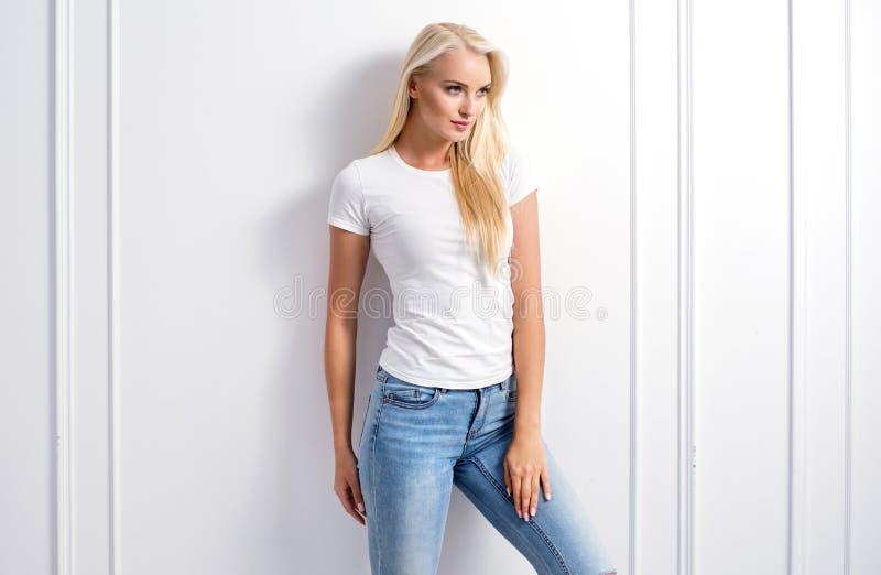 Junge blonde Frau, die auf einer dekorativen Wand sich lehnt stockfoto