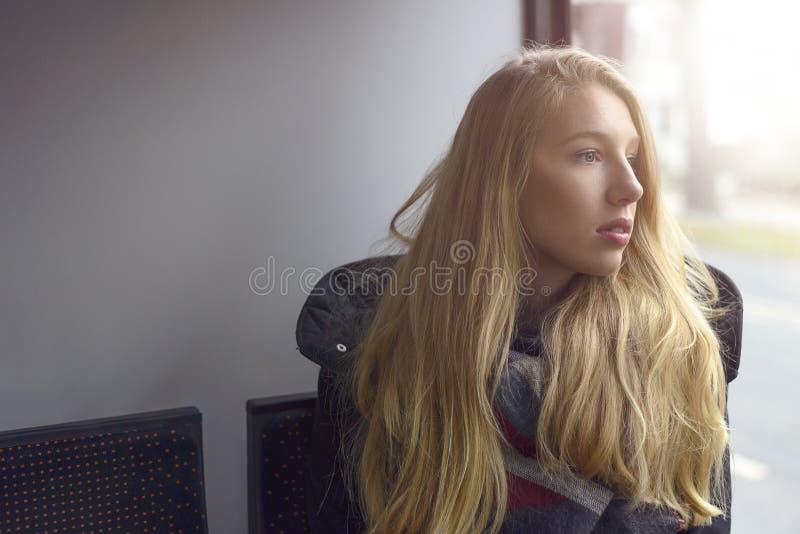 Junge blonde Frau, die aus heraus Fenster schaut lizenzfreies stockfoto