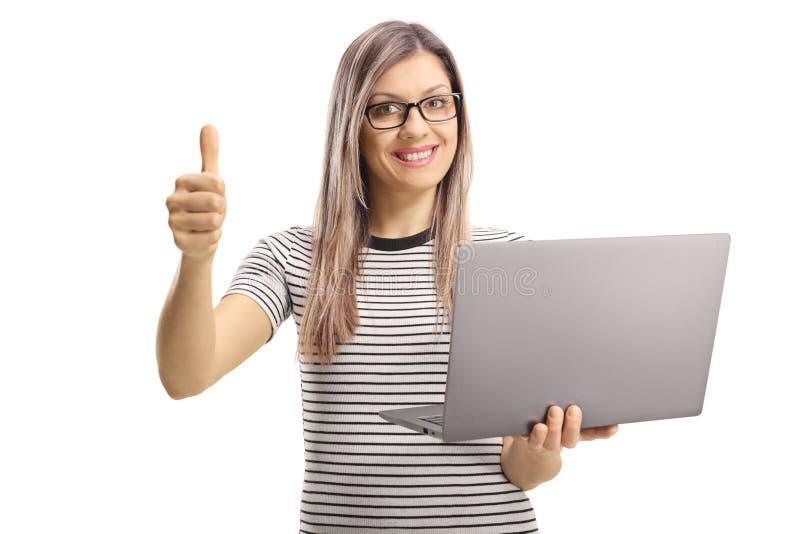Junge blonde Frau, die eine Laptop-Computer hält und sich Daumen zeigt lizenzfreies stockfoto