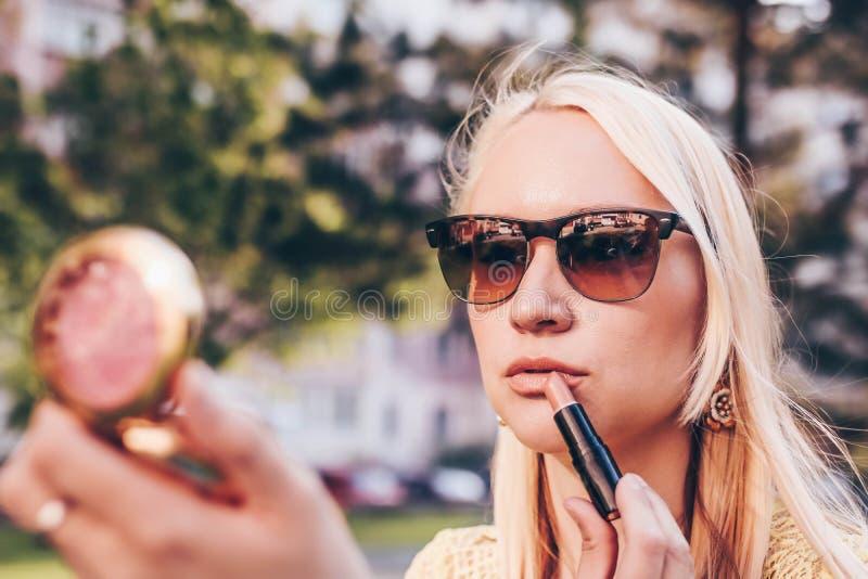 Junge blonde Frau, die in einem kleinen Spiegel in der Stra?e und im corret ihr Lippenstift schaut stockfotografie