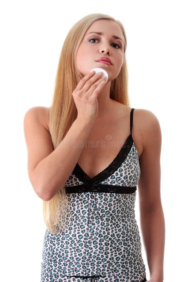 Junge blonde Frau, die Gesichtsbaumwolauflagen verwendet. stockfoto