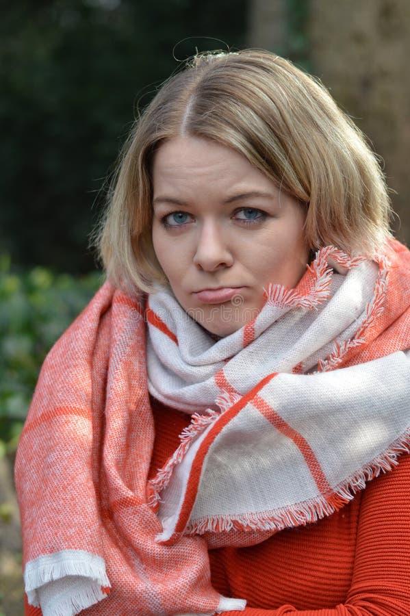 Junge blonde Frau, die ihren Mund fragend schürzt stockbild