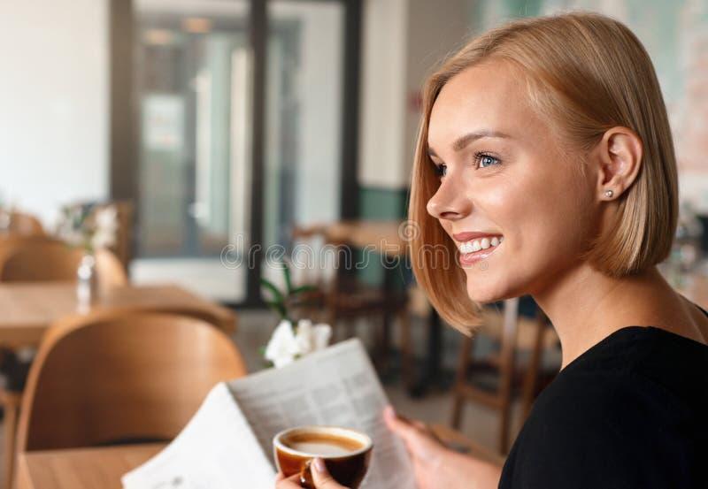 Junge blonde Frau, die im Café mit einer Zeitung zum Lesen von Kaffee frühstückt stockbild