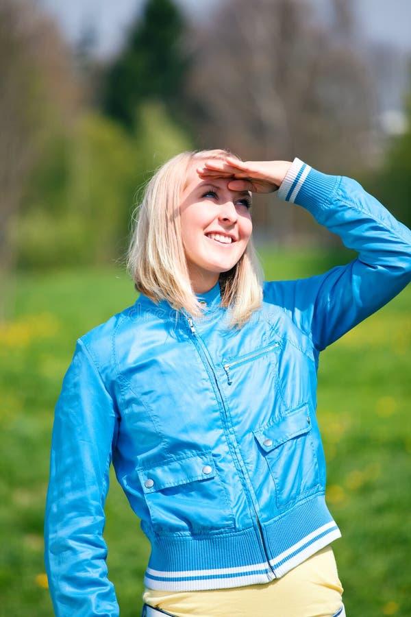 Junge blonde Frau, die im Frühjahr Himmel schaut stockfoto