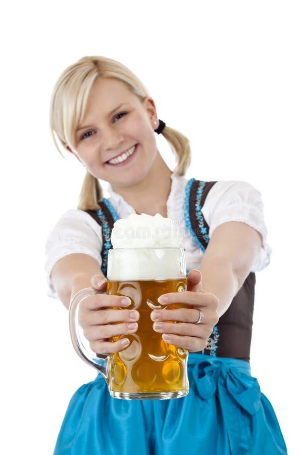 Junge blonde Frau im Dirndl röstet mit Bier Stein lizenzfreies stockfoto