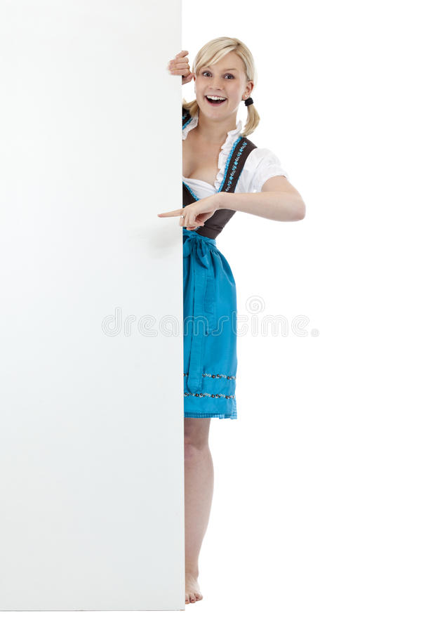 Junge, blonde Frau im Dirndl zeigend auf Anschlagtafel stockfotografie