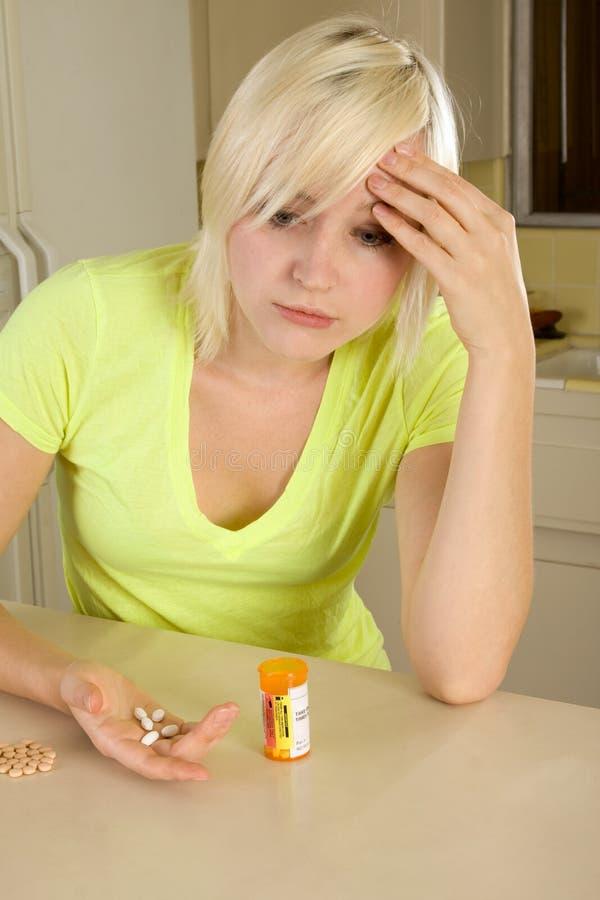 Junge blonde Frau mit Medizinpillen lizenzfreie stockbilder
