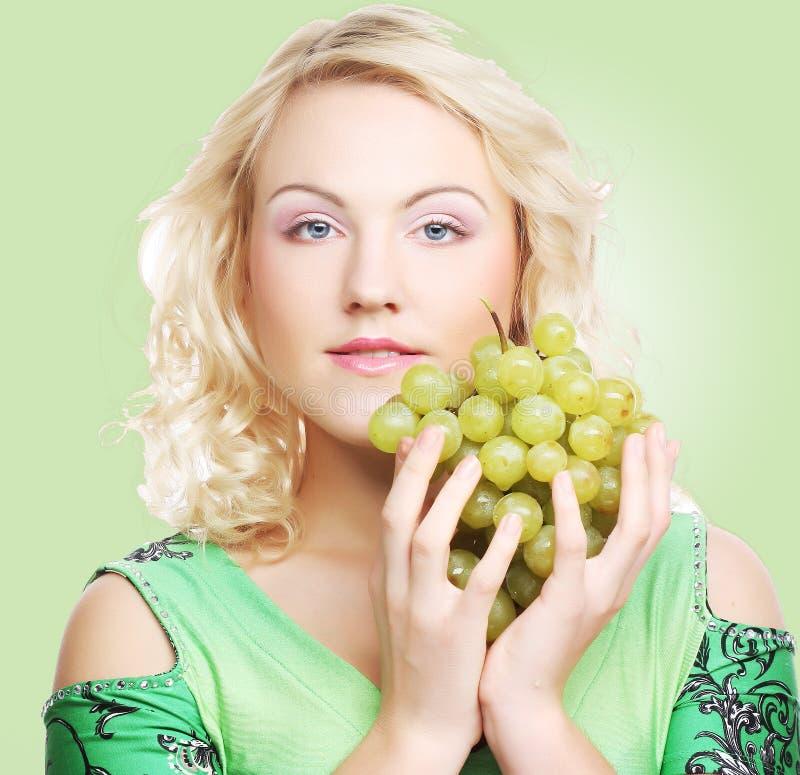 Junge blonde Frau mit Traube stockbilder