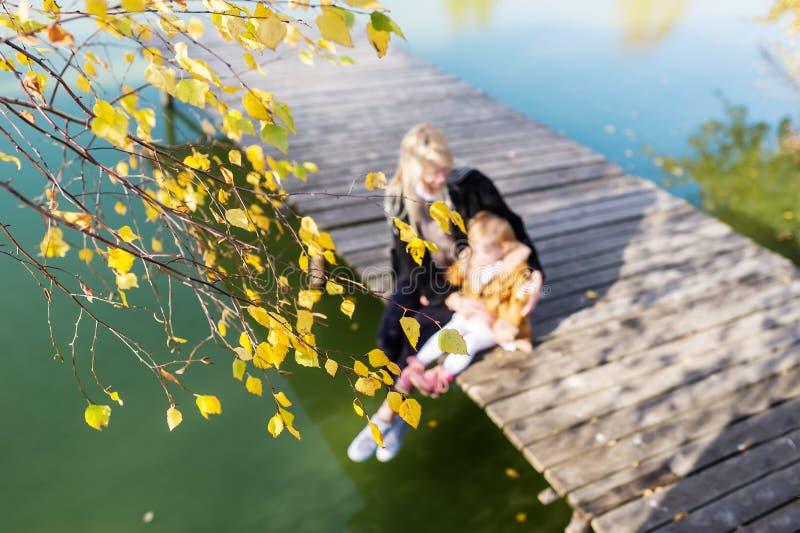 Junge blonde Mutter- und Babytochter, die auf dem Pier nahe dem See sitzt stockfoto