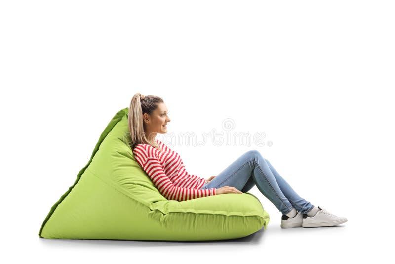 Junge blonde zufällige Frau, die auf einer Tasche der grünen Bohne sitzt stockfoto