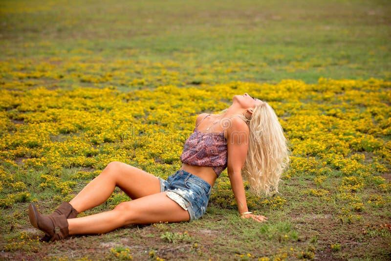 Junge Blondine auf dem Gebiet stockfotografie