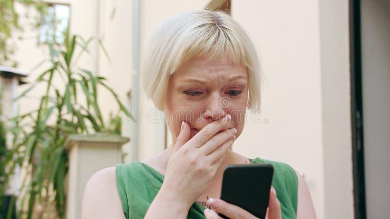 Junge Blondine, die außerhalb und unter Verwendung des Telefons sitzen lizenzfreies stockbild