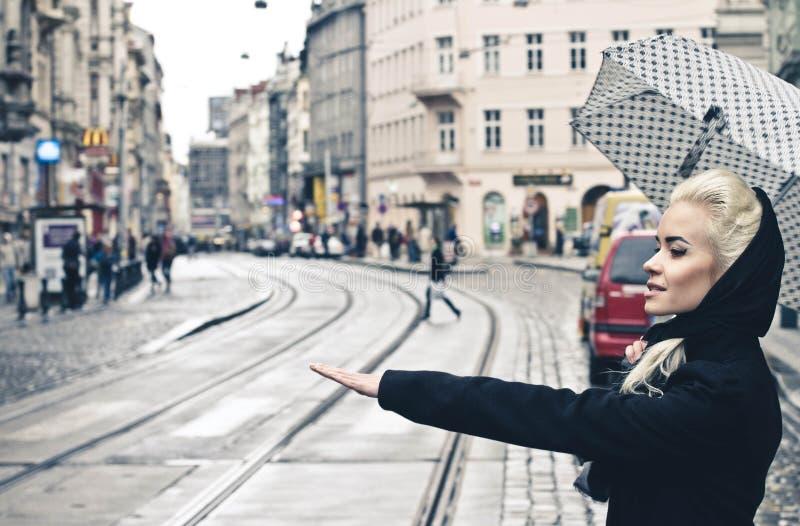 Junge Blondine, die das Taxi auf der Stadtstraße, elegantes Mädchen mit Regenschirm fangen lizenzfreie stockfotos