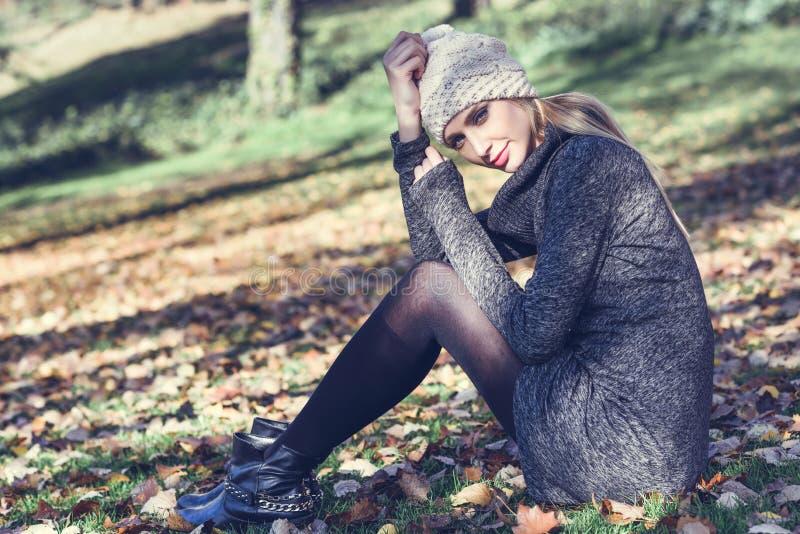 Junge Blondine, die in einem Park mit Herbstfarben sitzen lizenzfreie stockfotografie