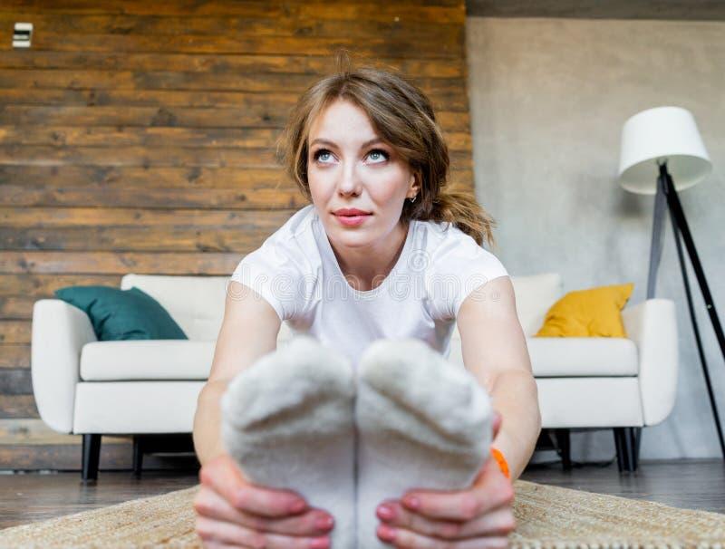 Junge Blondine, die Yoga?bungen zu Hause ausdehnend tun Gesunder Lebensstil lizenzfreie stockbilder