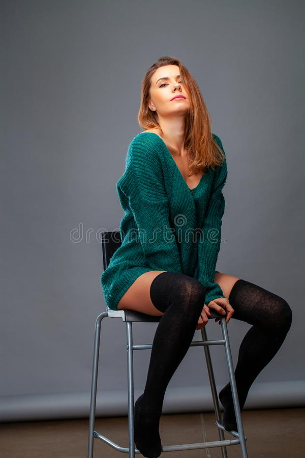 Junge Blondine in einer grünen woolen Strickjacke lizenzfreies stockbild