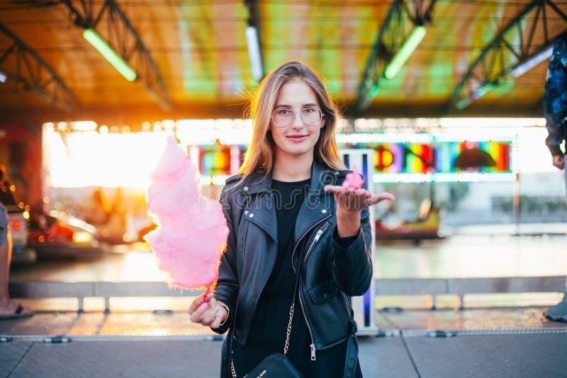 Junge Blondine essen Zuckerwatteglasschlacke lizenzfreie stockbilder