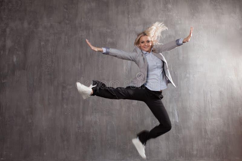Junge Blondine im Anzug und in Turnschuhen, die für Freude, grauer strukturierter Hintergrund springen stockbilder
