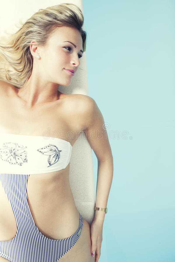 Junge Blondine mit dem Badeanzug, der am Rand eines Swimmingpools liegt lizenzfreie stockbilder