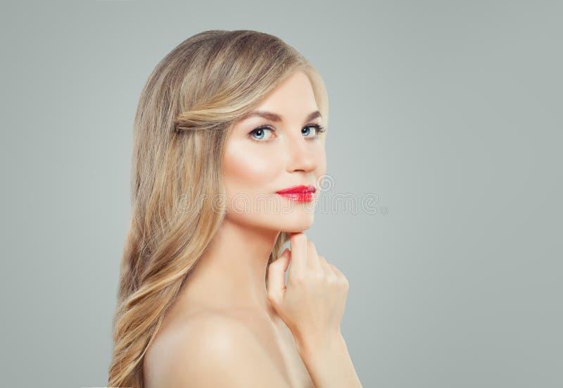 Junge Blondine mit dem langen Haar, klarer Haut und rotem Lippenmake-up Gesichtsbehandlungs-, Haarpflege- und Cosmetologykonzept stockfotografie