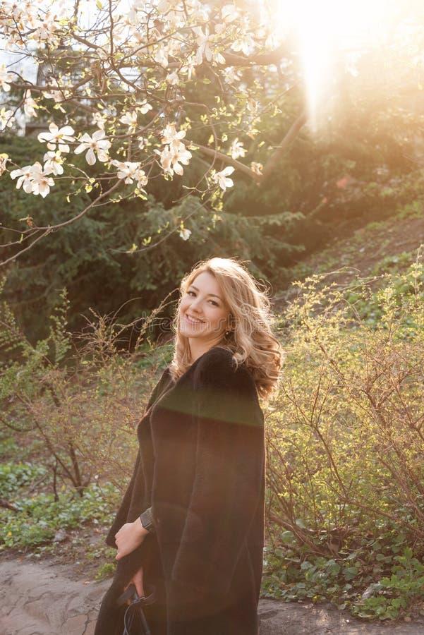 Junge Blondine nahe blühendem Park des Magnolienblumen-Baums im Frühjahr am sonnigen Tag Magnolienb?ume Sch?nes gl?ckliches lizenzfreies stockbild