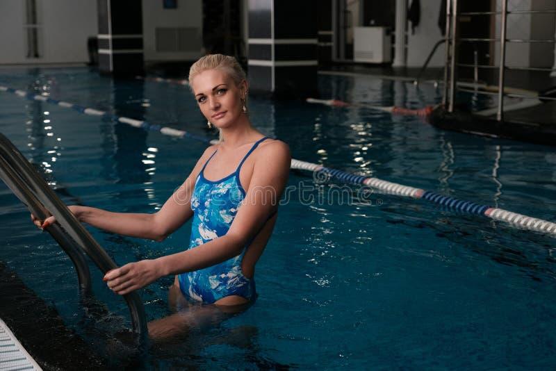 Junge Blondinestellung in einem geschlossenen Pool und Halten der Handläufe der Treppe, die Kamera betrachtend lizenzfreies stockbild