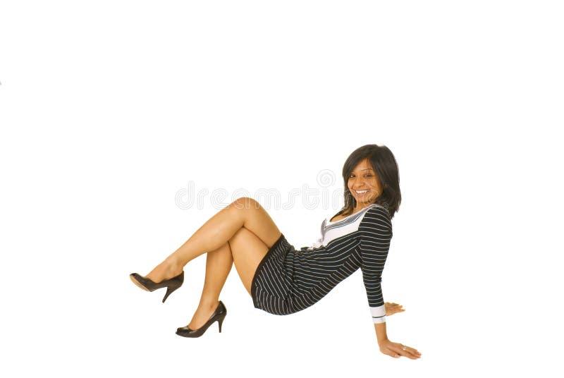 Junge braune Frau, die auf dem Fußboden aufwirft stockbilder