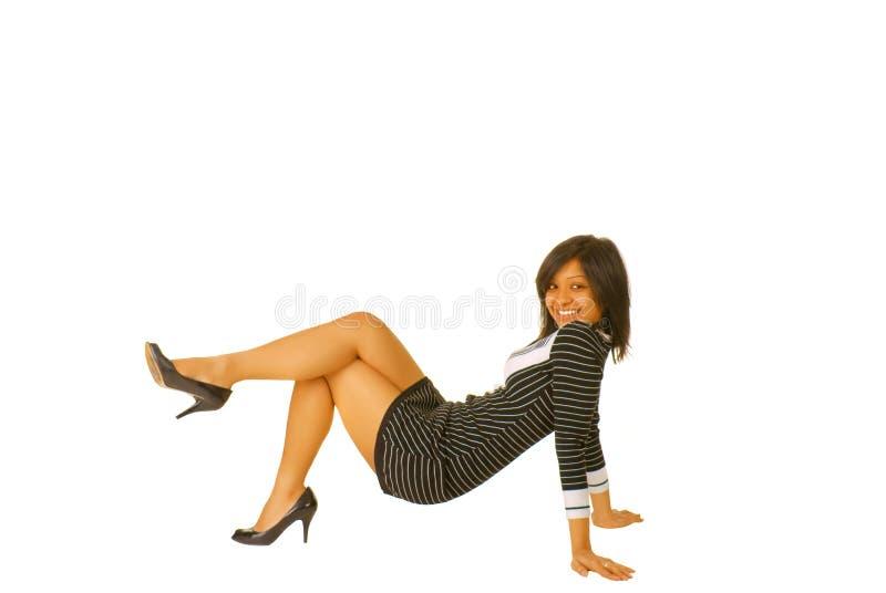 Junge braune Frau, die auf dem Fußboden aufwirft stockfoto