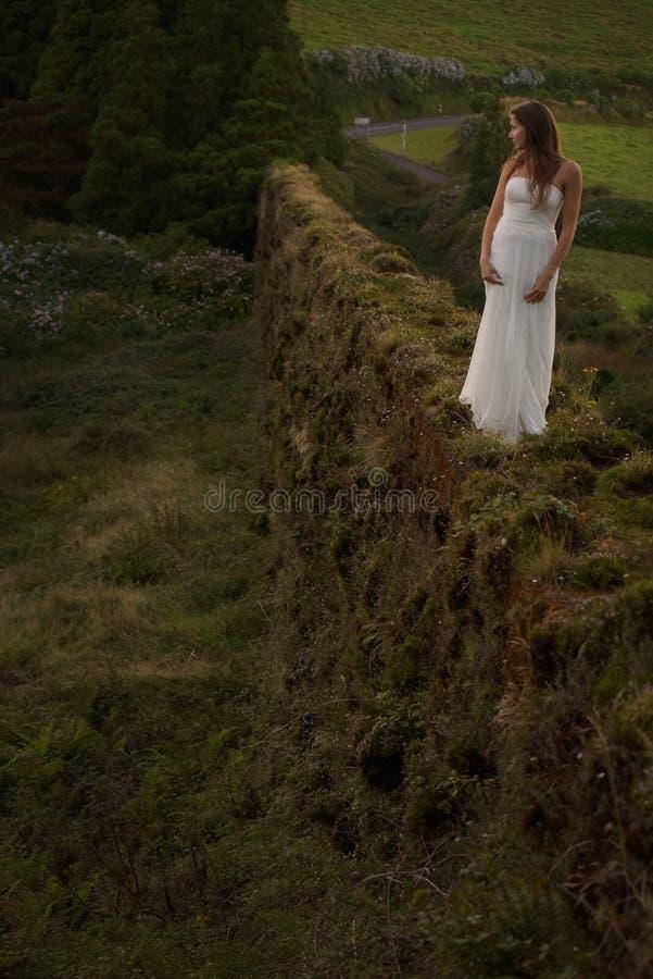 Junge Braut, die auf grasartigem brickwall in der grünen Landschaft von Sao Miguel Island steht lizenzfreie stockfotos