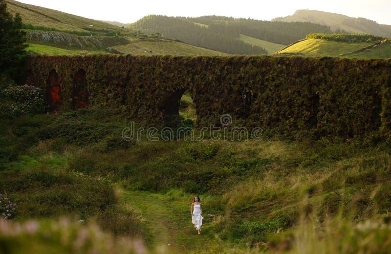 Junge Braut, die nahe grasartigem brickwall in der grünen Landschaft von Sao Miguel Island läuft stockbild