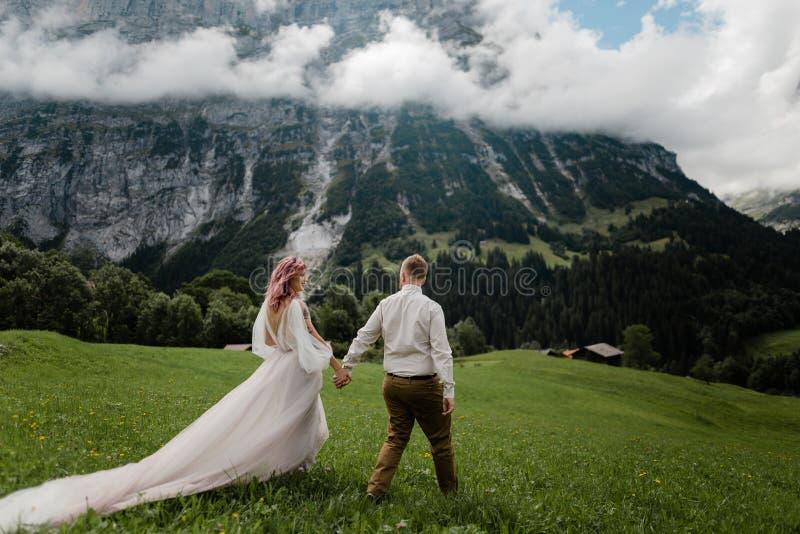 junge Braut im Hochzeitskleid und -bräutigam, die auf grüne Bergwiese mit Wolken gehen stockbilder