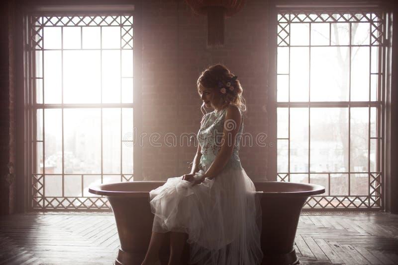 Junge Braut im Kleid, Schattenbild auf Fensterhintergrund sitzt gegen das Licht stockfoto