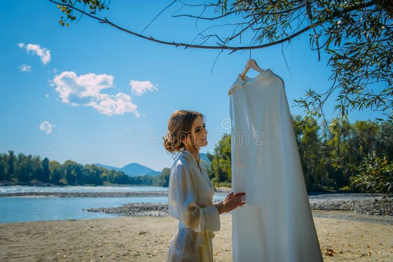 Junge Braut interessiert sich Hochzeitskleid in der wilden Natur nahe Fluss stockbild