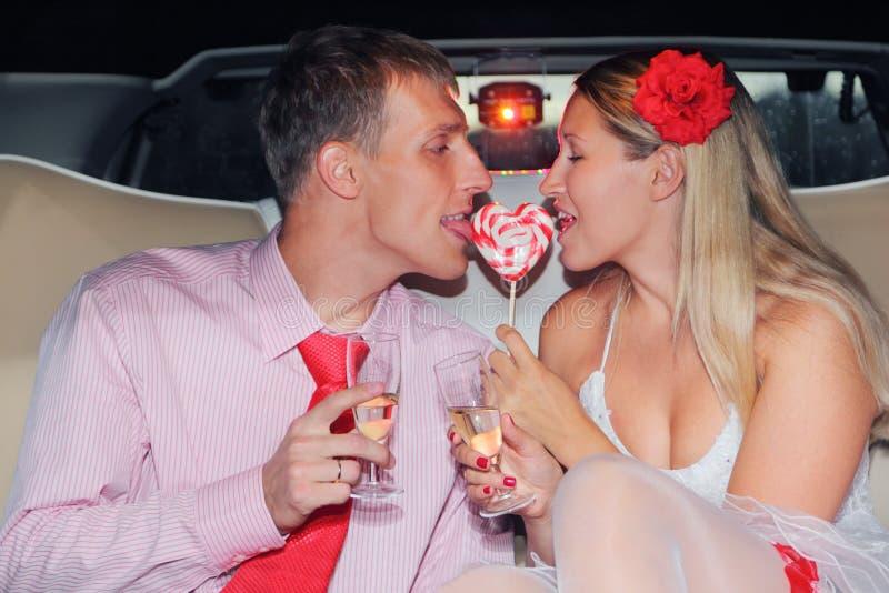 Braut und Bräutigam sitzt im Auto, Griffglas des Champagners stockbilder