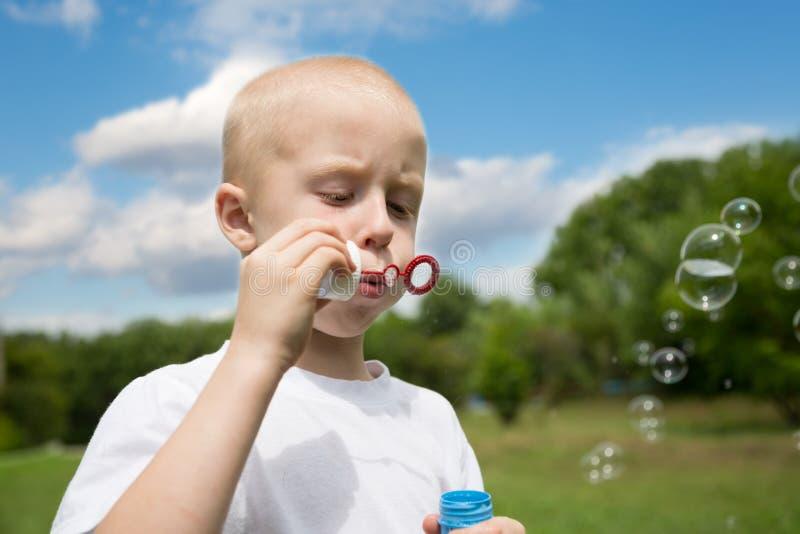 Junge brennt Seifenblasen im Park durch lizenzfreie stockfotografie