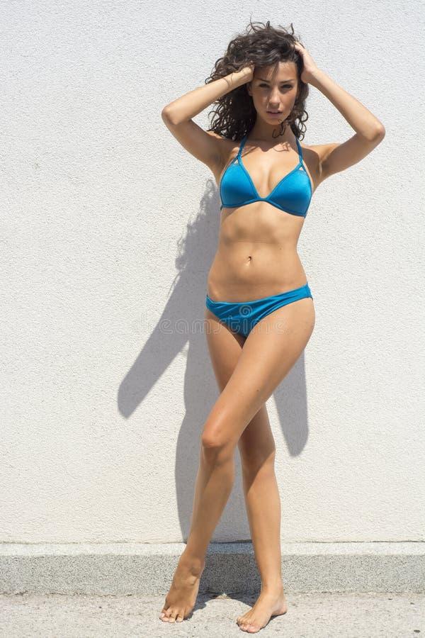 Junge Brunete-Frau, die auf Sonne im Bikini aufwirft stockfotos